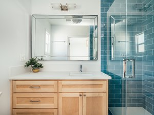 bathroom with teal subway shower tile, glass shower door, light wood bathroom vanity, rectangular mirror with overhead lighting