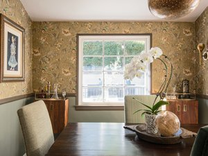 Dining room with floral wallpaper and wood storage cabinets