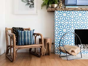 Living room with blue tiled fireplace and wood chair and side table
