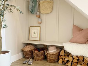 Under the stairs storage in small mudroom with baskets and seating