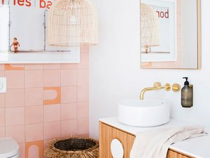 bathroom lighting idea with pink wall and floor tile and floating wood vanity with pendant