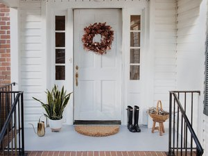 Freshly painted concrete porch with gray paint, wreath on door, entry rug, planter, boots and watering can