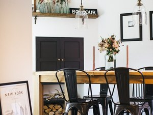 industrial dining room idea with iron chairs and exposed glass lighting