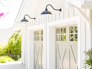 Cream barn garage doors with white exterior and black barn lights