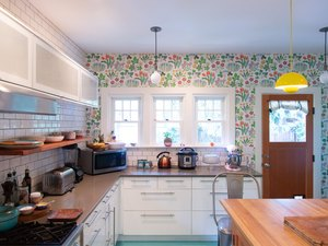 kitchen with floral wallpaper, white cabinets, green floor