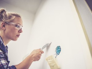 Young woman renovating her home, using wall repair kit and putty knife