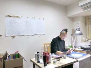 Artist Martin Hsu at his desk in his temporary studio in Taiwan