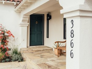 A white Mediterranean-style home entrance with black address numbers