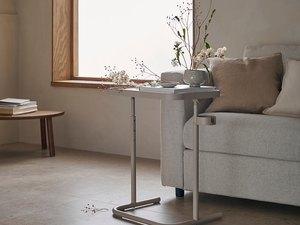 IKEA Björkåsen laptop stand in beige with vases of flowers on top