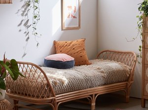 Small Space Daybed Ideas with Rattan daybed, pillows, plants, art, rug.