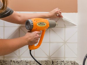 Use a heat gun to warm the surface of the peel-and-stick wallpaper.