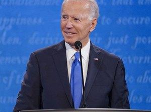 joe biden standing at podium wearing blue tie over blue background