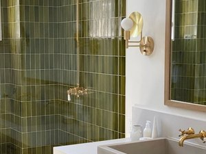 brass shower fixtures with vertically stacked green tile