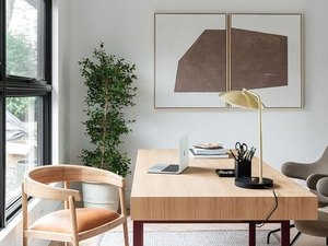 white modern home office with  large desk in the center and wall art hanging above