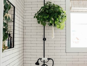 Black plumbing fixtures with clawfoot tub and subway tile