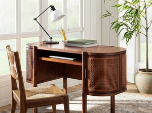 cane desk with chair near windows and plant
