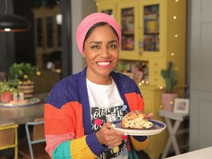 nadiya hussain in kitchen holding plate with baked good