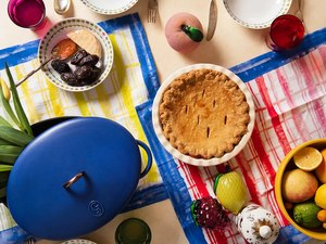 tabletop with dutch oven, pie, colorful towels, and other food items