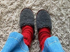 person wearing grey ikea fegen slippers with red socks and jeans on white stringy carpet