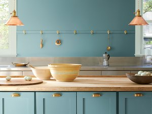kitchen with teal wall and cabinets and bowls on counter