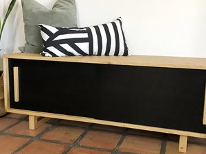 DIY storage bench in a black and wood finish with sleek handles and throw pillows