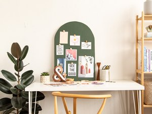 DIY Arched Mood Board sitting on white desk next to plant and bookshelf