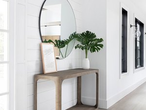 Modern Hallway with console table, mirror, plant, wood floors.