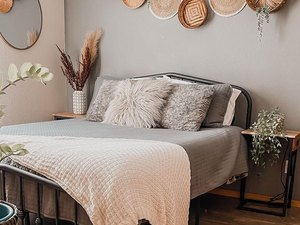 basket wall decor above bed with grey linens and white waffle throw blanket