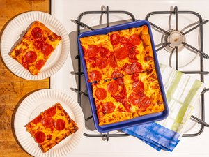 blue small sheet pan with pizza on stovetop
