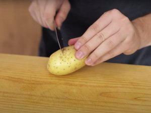 person cutting a line around the center of a potato