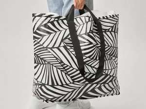 person with blue jeans holding black and white patterned bag
