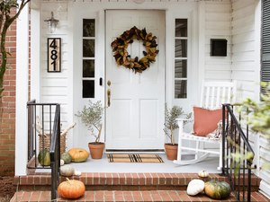 Fall porch with wreath, pumpkins, rocking chair, house numbers, and firewood stored in basket