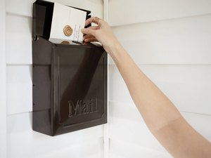 Black mailbox with hand adding letter