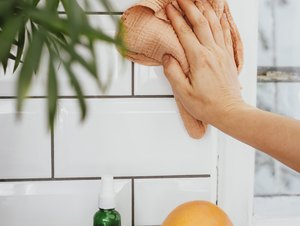 Cleaning kitchen tile with cloth, and lemons