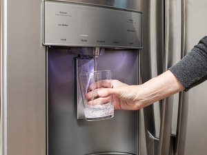 Water from refrigerator filter system filling glass