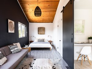 small spaces in Bold boho bedroom with wood floor and ceiling, gray-black accents and a white minimalist office