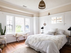 Boho white-walled bedroom with wood floors and woven decorative furnishings