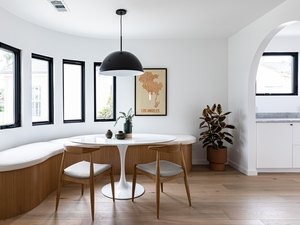 eco-friendly home design with contemporary curved dining room with curved bench, small round table, chairs, pendant lamp, and tall windows with view of hallway via archway