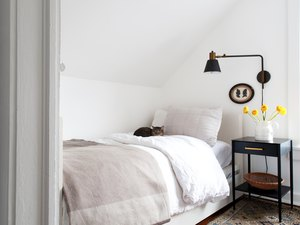 Bedroom with white bedding and walls with dark farmhouse lamp and nightstand