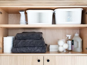 laundry storage on wood shelving with white bins and glass canisters