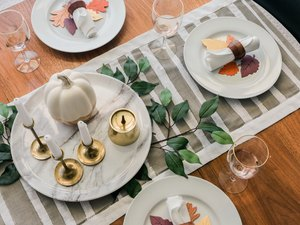 Minimalist striped table runner with dishware and foliage decor on wood table