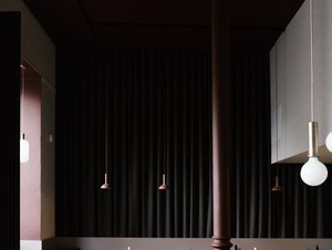 Dark minimalist bar with dark brown and black dining furniture and pendant lights