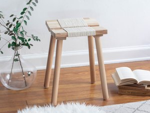 IKEA wood stool with rope on wood floor with plant in clear vase and stack of books