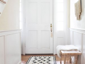 Hallway Runner Ideas in White hallway with geometric black-white jute rug on wood floor with basket