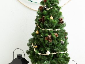 Small DIY Christmas tree with mini ornaments on black and white countertop with lanterns against white wall with decorative hanging bead chains