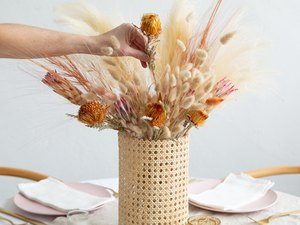 Cane vase with dried flowers and grass on dining table