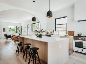 White and wood kitchen with black stools and black pendant lights.
