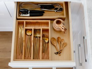 An open drawer with a wooden utensil drawer organizer, cold cutlery, and various other utensils.