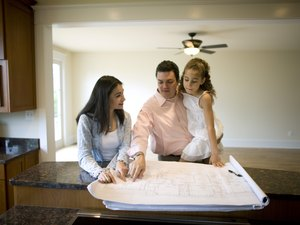 Family looking at blueprints in new home