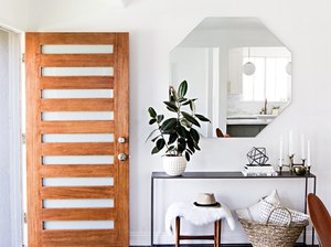 An entryway mirror without a frame in a modern home.